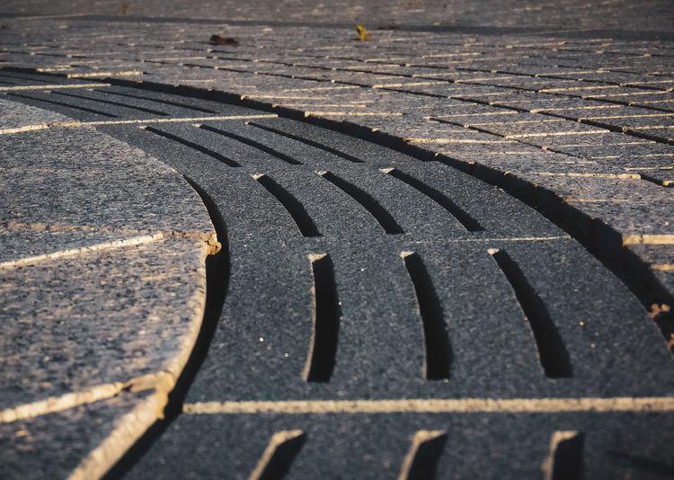 Close-up of manhole on cobblestone street