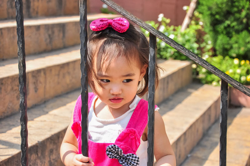 Cute girl standing against railing