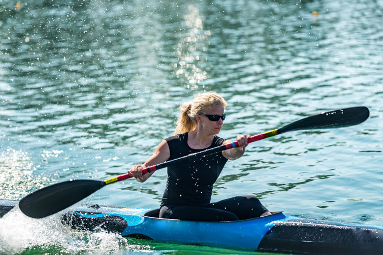 Female Kayaker Training On lake Kayak Kayaking Kayak Paddles Kayaker Woman Training Exercising Sport Female Water Adventure Activity Summer Leisure Activity Canoe Nature Outdoor Active Rowing Lifestyle Young Boat Lake Recreation  Competition