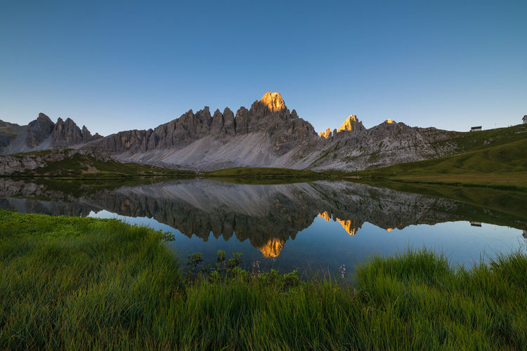 Sunlight reaching the peaks of Dolomiti mountains above Laghi del Piani Beauty In Nature Blue Clear Sky Dawn Day Dolomites Dolomiti Grass Green Color Italy Lake Landscape Majestic Mountain Mountain Range Nature Outdoors Reflection Scenics Sunlight Sunrise Tranquility Travel Destinations Water