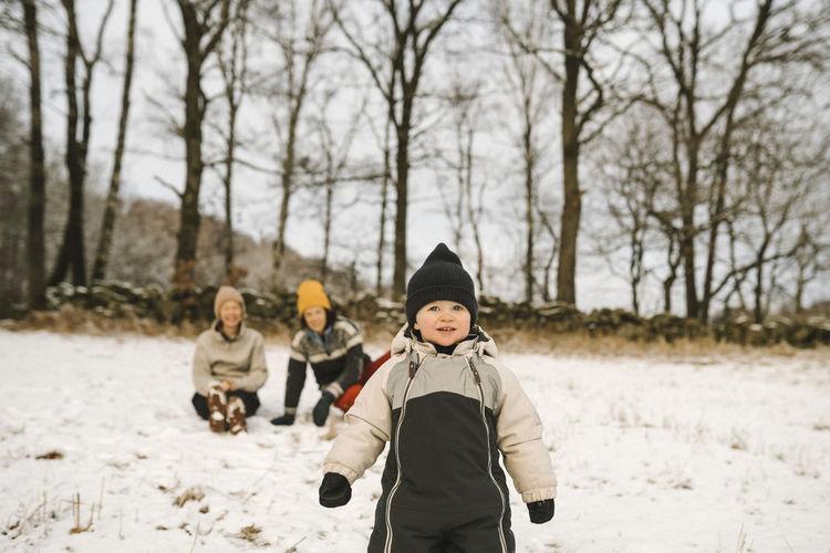 Full length of boys on snow covered trees