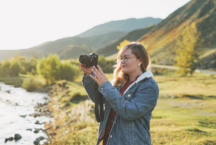 Beautiful smiling blonde young woman traveler with photo camera in hands, trip to the mountains