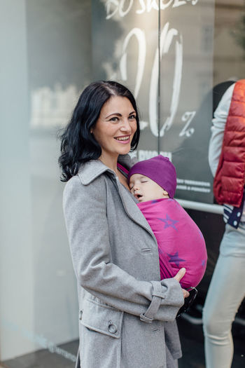 Happy mother wearing her sleeping child in woven wrap. Portrait of trendy woman carrying her little baby in sling whilst shopping in the city. Baby Babywearing Motherhood Carry Carrier Wrap Sling Child Infant Wear Attachment Parenting Woman Relationship Bonding Closeness Togetherness Together Woven Caucasian Love Ergonomic City Safety Sleeping