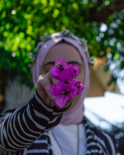 Close-up of woman holding purple flowers