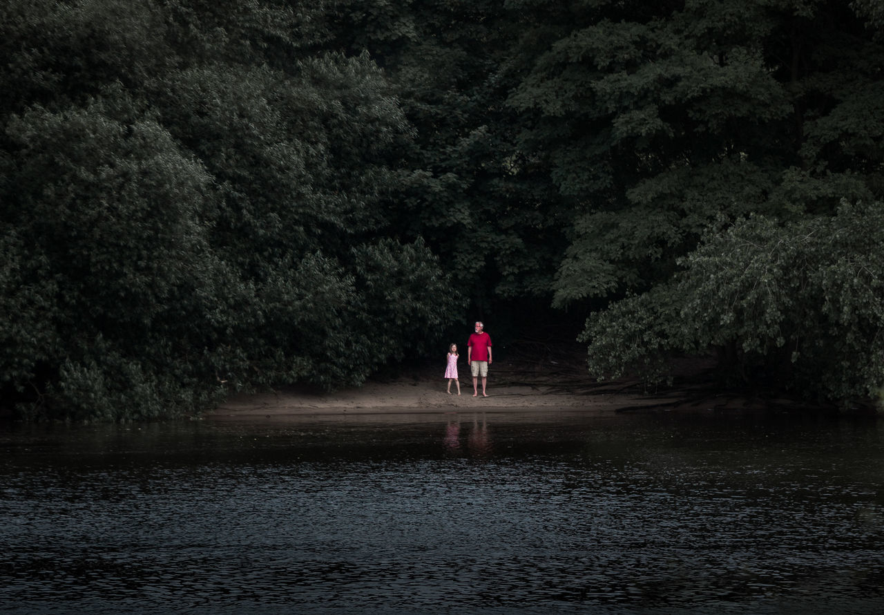 FULL LENGTH OF MAN WITH UMBRELLA ON WATER