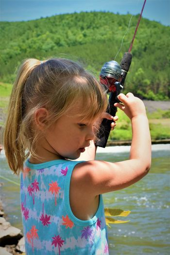 Close-up of cute girl fishing in river