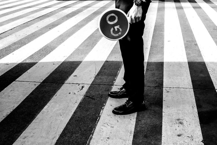 Low section of man standing on zebra crossing