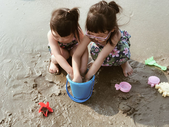High angle view of siblings playing at beach