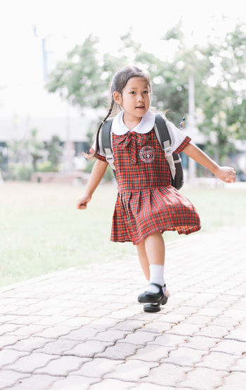 Full length of schoolgirl looking away while running on footpath