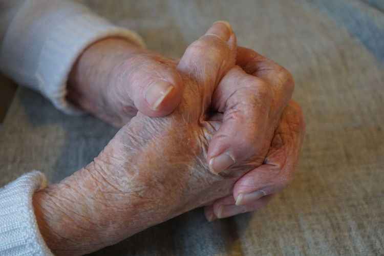 Elderly Woman Elderly Hands Old Woman Human Hand Human Body Part Hand Real People Body Part One Person Men Indoors  Finger Senior Adult Human Finger Close-up High Angle View Wrinkled Human Skin Wood - Material Table Lifestyles Skin Human Limb Care Human Foot