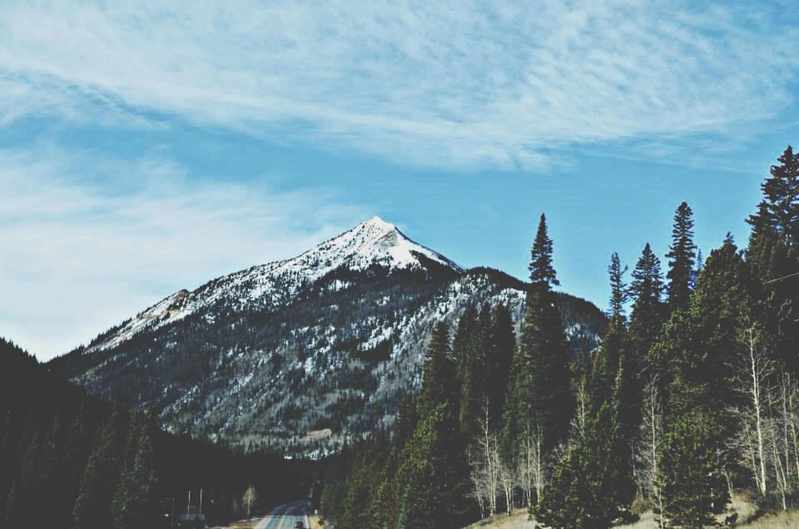 mountain, sky, snow, cold temperature, tranquility, scenics, cloud - sky, winter, beauty in nature, tree, tranquil scene, low angle view, nature, mountain range, weather, cloud, cloudy, snowcapped mountain, day, season