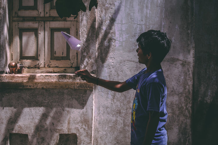 Side view of smiling boy throwing paper airplane by old house