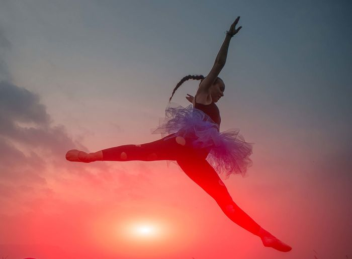 Low angle view of woman dancing against sky during sunset