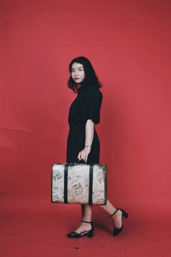 Portrait of young woman with luggage standing against red background