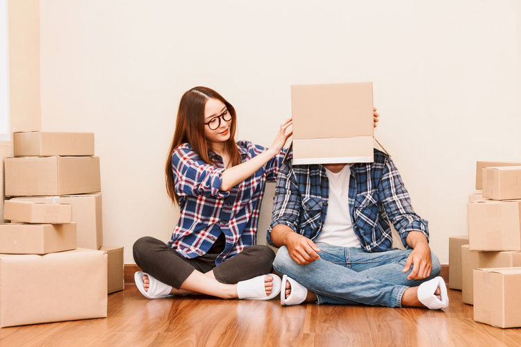 Happy couple with cardboard box at new home Adult Beginnings Box Box - Container Cardboard Cardboard Box Casual Clothing Change Flooring Full Length Hardwood Floor Home Improvement Indoors  Lifestyles Moving House Packing Relocation Sitting Smiling Unpacking Wireless Technology Women Wood Young Adult Young Women