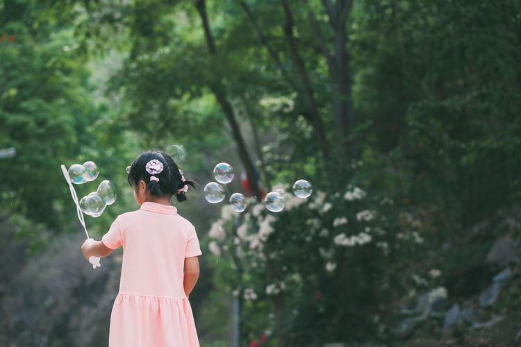 Portrait of funny asian little girl is blowing soap bubbles Bubble Bubble Wand Day Focus On Foreground Growth Hairstyle Holding Leisure Activity Lifestyles Nature One Person Outdoors Plant Real People Rear View Standing Three Quarter Length Tree Waist Up Women Young Adult