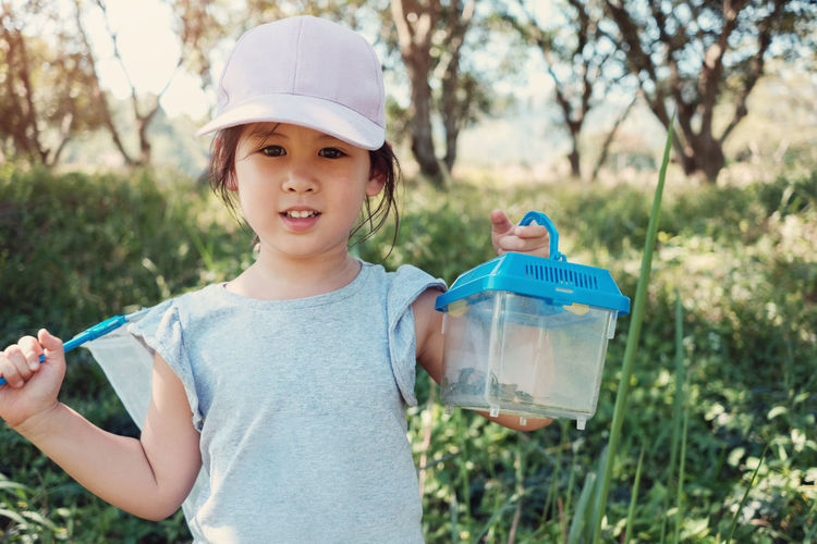 Cute Asain girl catching butterfies with a net and holding a box of insects, outdoor activity for kid, homeschooling education and learn through play concept Butterfly Box Catch Fun Happy Kids Learning Lifestyle Nature Activity Child Childhood Container Education Girl Homeschooling Insect Leisure Activity Montessori Nature Outdoors People Play Smile Spring