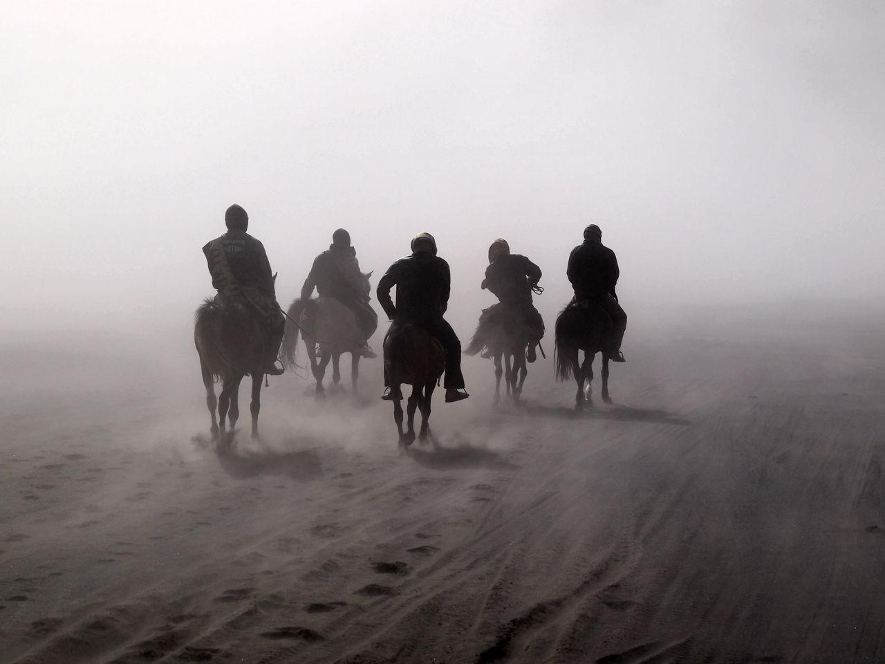 PEOPLE WALKING ON SAND DUNES IN DESERT