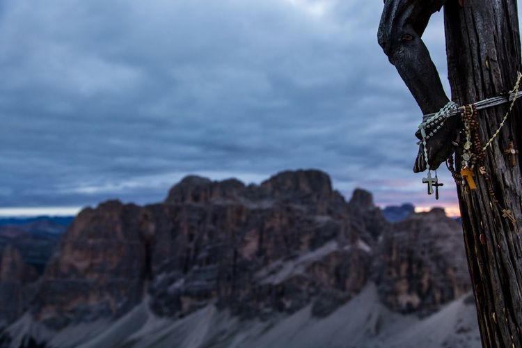 Crosses hanging on crucifix by rocky mountains against cloudy sky