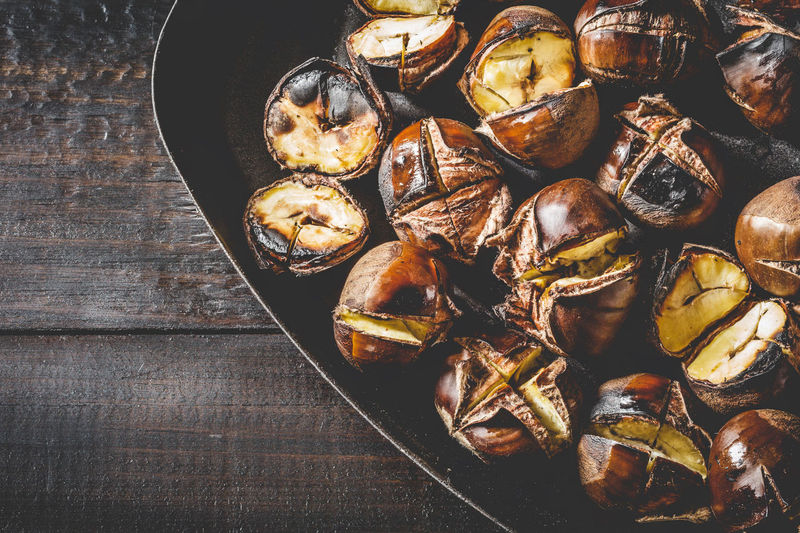 Roasted chestnuts in cast iron grilling pan over rustic wooden board. Autumn Chestnut Chestnuts Cooking Iron Meal Snack Brown Food Fried Fruit Gourmet Healthy Heap Ingredient Nut Opened Pan Roasted Roasting Seasonal Sweet Tasty Traditional Wooden