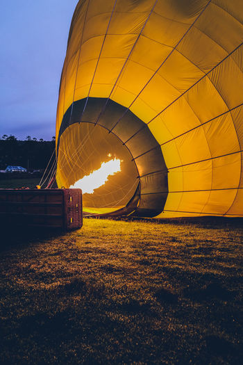 View of hot air balloons on field during sunset