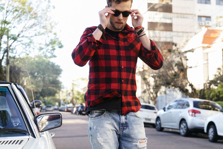 Adult Car Casual Clothing Day Land Vehicle Mode Of Transport One Person Outdoors People Real People Standing Sunglasses Transportation Young Adult Young Men