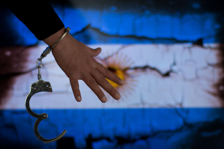 Cropped hand of male criminal with handcuffs against argentinian flag