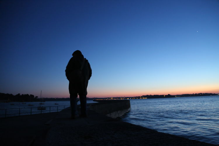 Rear view of man standing on pier at beach against sky