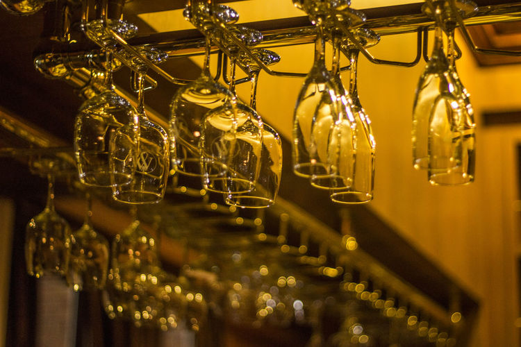Upside down view of wineglasses on table in illuminated restaurant