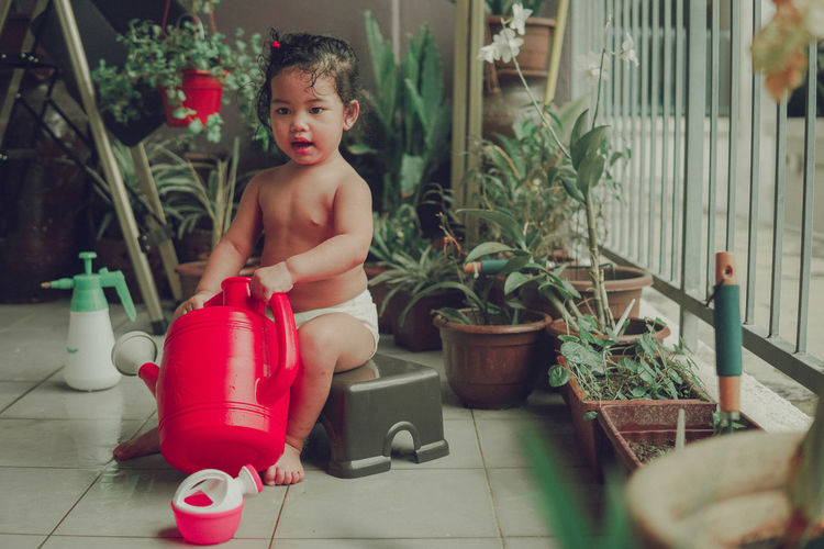 Cute boy playing in potted plants