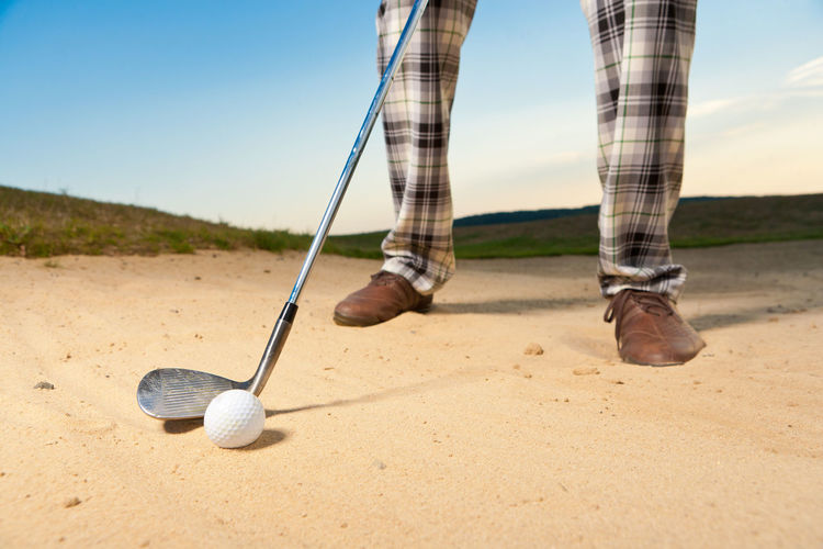 Low Section Of Man Playing Golf On Sand