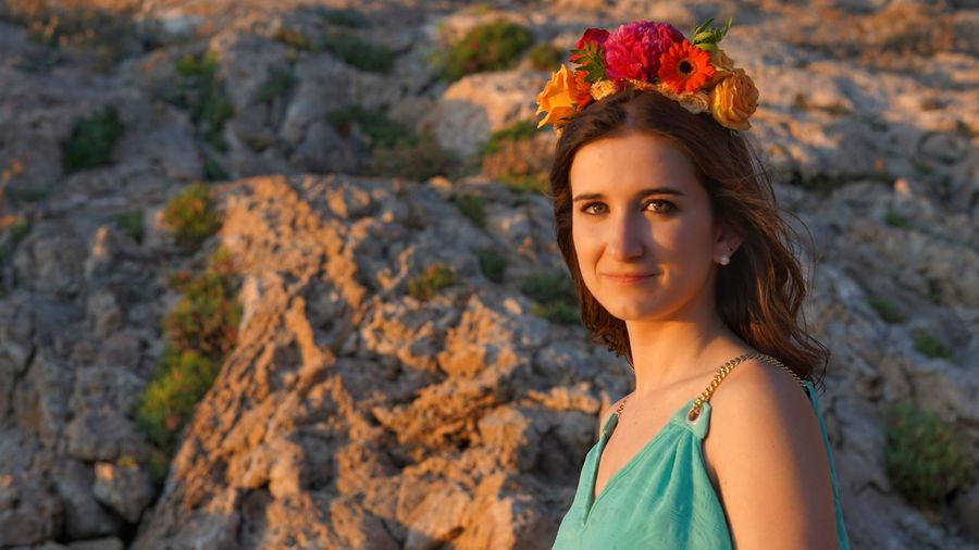 Portrait of beautiful young woman on rock