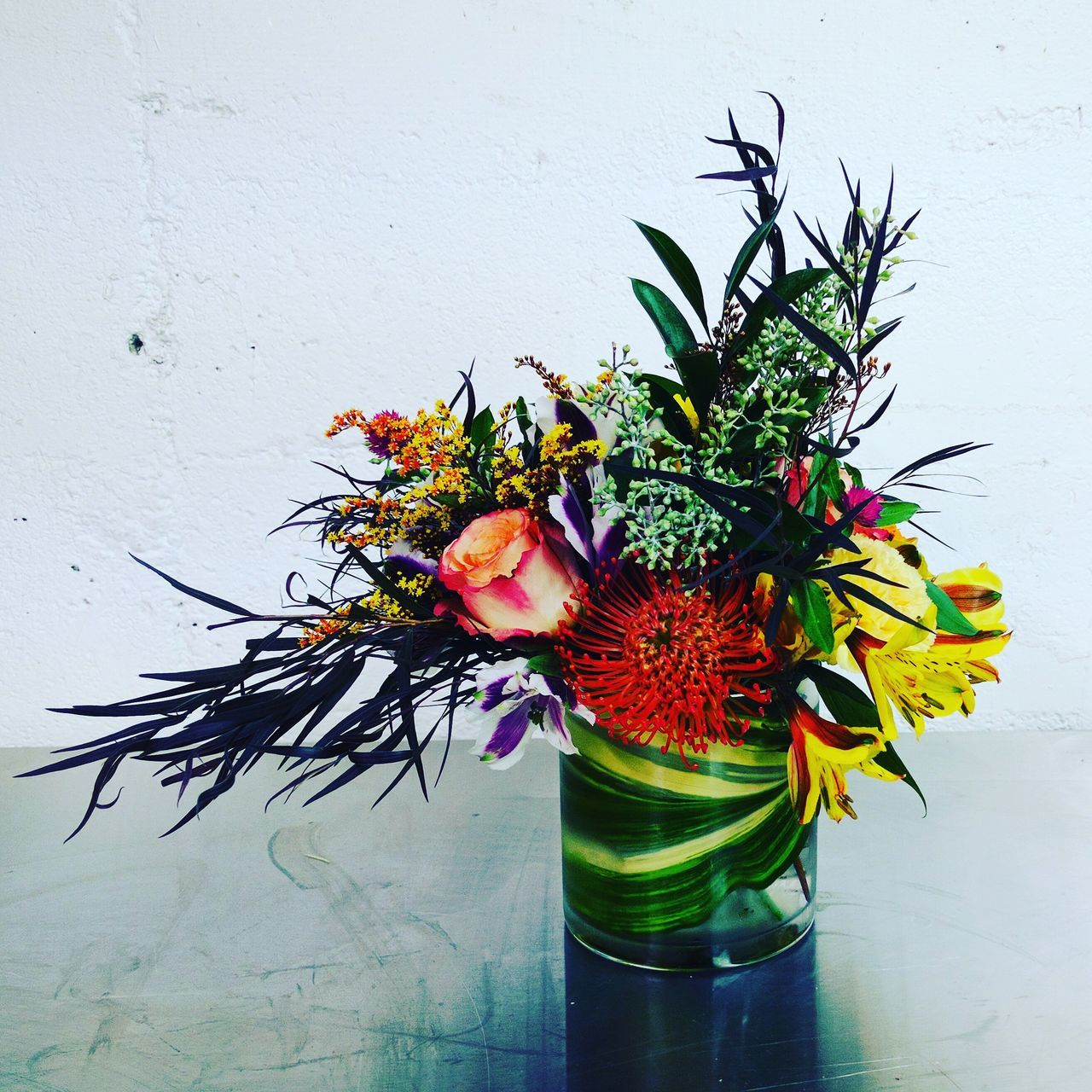 flower, wall - building feature, vase, plant, no people, nature, table, leaf, green color, beauty in nature, growth, freshness, fragility, indoors, day, multi colored, close-up, flower head