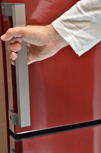 Hand on door handle of a red refrigerator