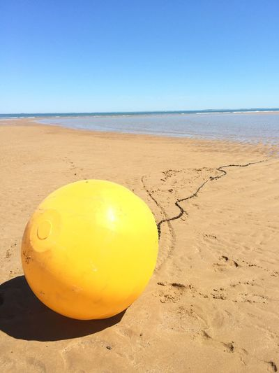 Yellow buoy on beach against clear blue sky