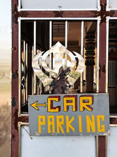 Arts And Crafts Chandigarh India Indian Culture  Painted Parking Sign Architecture Arrow Sign Capital Letter Communication Day Focus On Foreground Handmade Information Metal No People Outdoors Parking Refection Script Sign Sikh Text Western Script Yellow