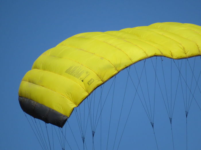 Low angle view of yellow parachute against clear sky
