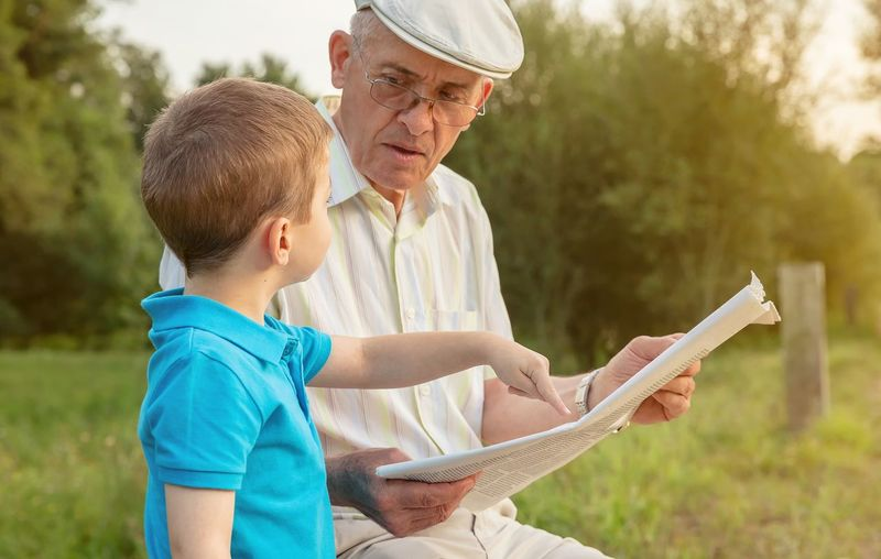 Closeup of senior man reading newspaper and cute child pointing an article with his finger sitting over a nature background. Two different generations concept. Mature Caucasian Age Hat Parent Together Education Sitting Male Adult Background Defocused Happy Leisure Lifestyle Old People Real Two Elderly Nature Family Learning Teaching Generation Closeup Outdoors Grandparent Grandfather Grandchild Grandson Park Bench Article Notice Report Hand Finger Pointing Looking Reading Paper News Newspaper Boy Kid Child Man Senior