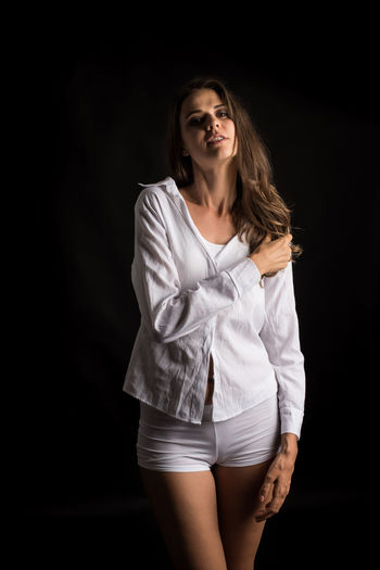 Black Background Studio Shot One Person Young Adult Three Quarter Length Women Beautiful Woman Beauty Indoors  Adult Portrait Front View Young Women Long Hair Hair Standing Beautiful People Clothing Fashion Hairstyle Shorts