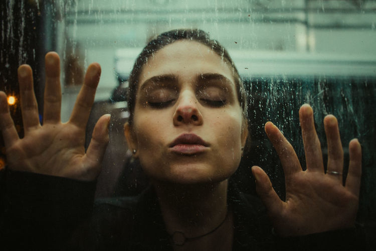 Close-Up Of Young Woman Touching Glass Window