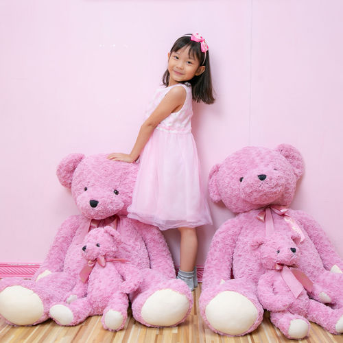 Cute girl with pink toy against wall