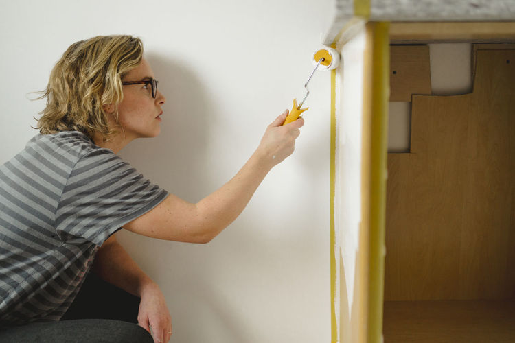 Side view of woman wearing eyeglasses on wall at home