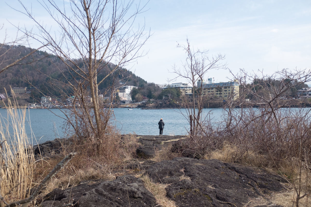 Person Standing On Lakeshore Against Sky