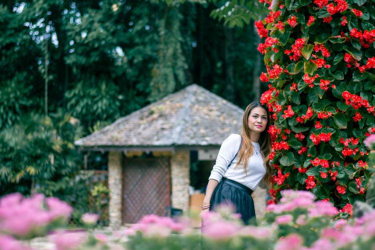 A woman is enjoying the nature of a flower garden.