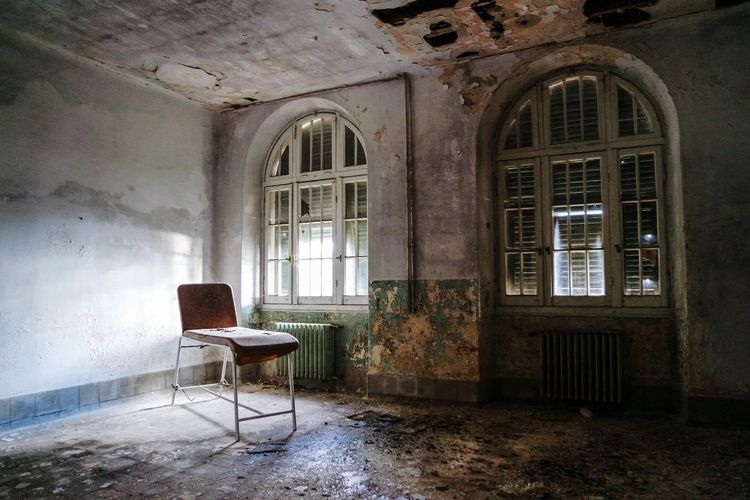 Empty chair and table in abandoned room