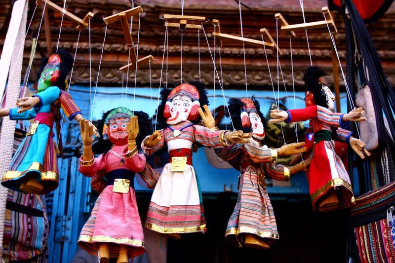 Low angle view of puppets hanging against house