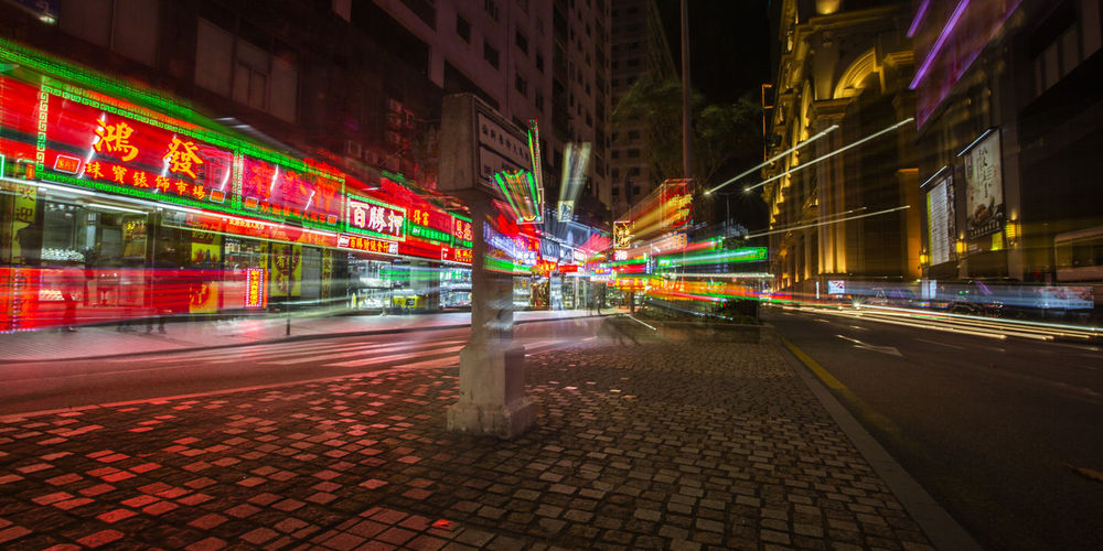 Light trails on street amidst illuminated buildings in city at night