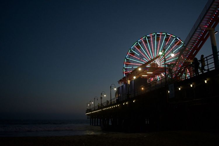 Low Angle View Of Illuminated Ferris Wheel On Pier By Sea At Night