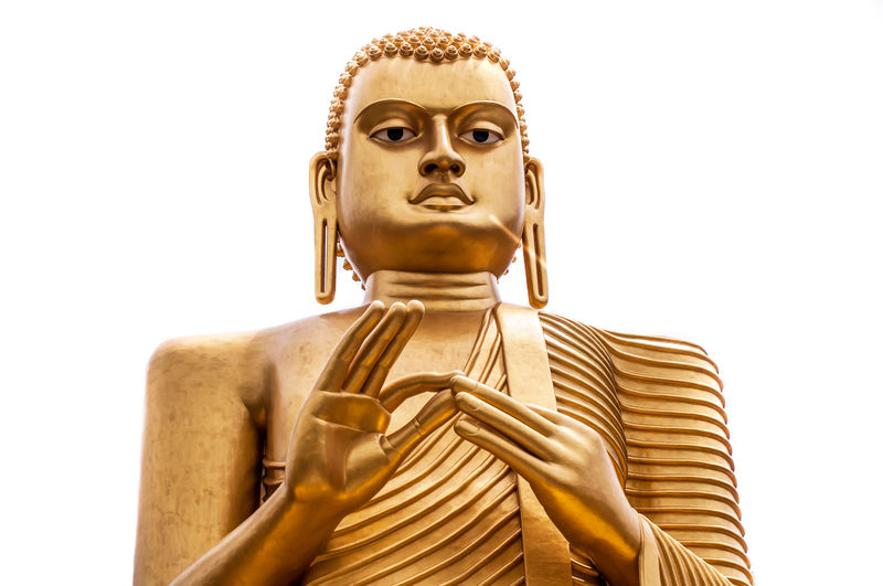 Low angle view of golden buddha statue against clear sky