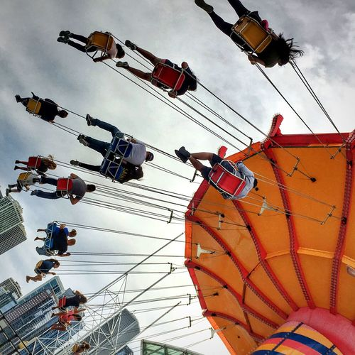Low angle view of people enjoying chain swing ride at navy pier